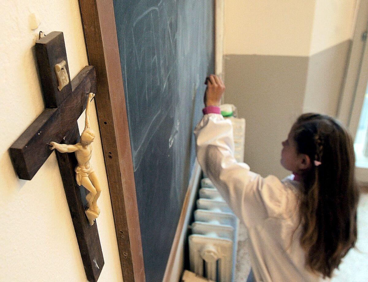 Una alumna de Religión escribe en la pizarra.