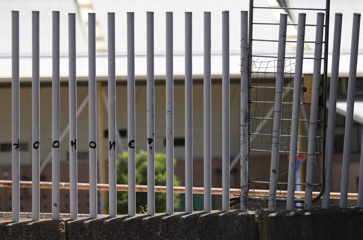 Una valla metálica de tráfico colgada en un hueco del vallado por donde se accede a la caseta ocupada.